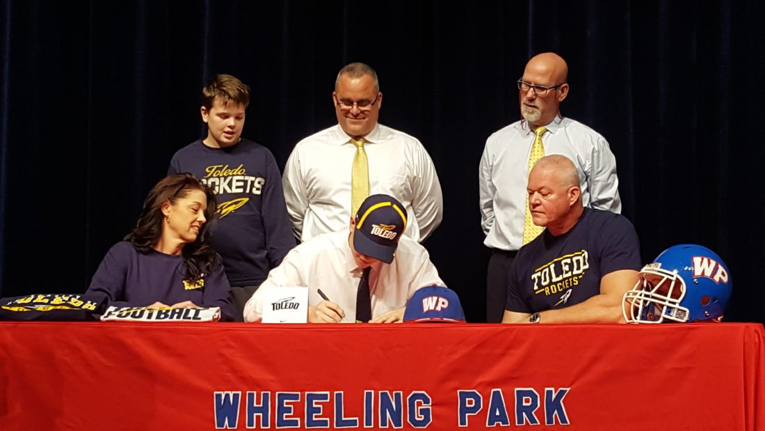TOLEDO BOUND — Wheeling Park quarterback Cross Wilkinson signed his letter of intent to continue his academic and athletic careers at the University of Toledo. Wilkson is flanked by his mother, Debbie, and father, Jeff. Back row, from left, is brother, Cole; Wheeling Park football coach Chris Daugherty and athletics director Dwaine Rodgers. (Photo by Shawn Rine)