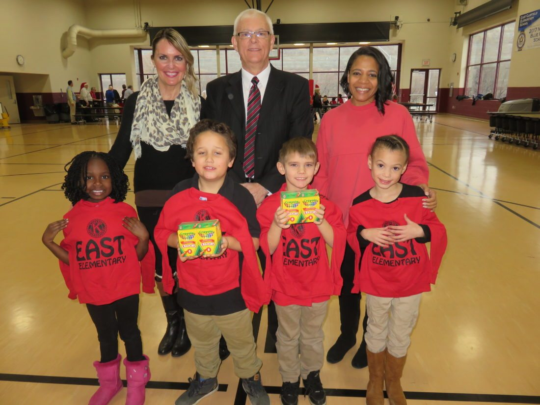 PARTYMOMENTS — East Elementary School first-graders, from left, front, Cherish Bryant, Brandon McCallister, Tyler Rhynehart and Denise Manley show off their sweatshirts and other gifts presented to them as part of the Steubenville Kiwanis Club's annual Christmas party held Dec. 12 for the first-grade classes there. With them are, back, from left,  Kristin Babela, first-grade teacher; Kiwanian Tom Timmons, event chair; and Aimee Livingston, club president.  -- Janice Kiaski