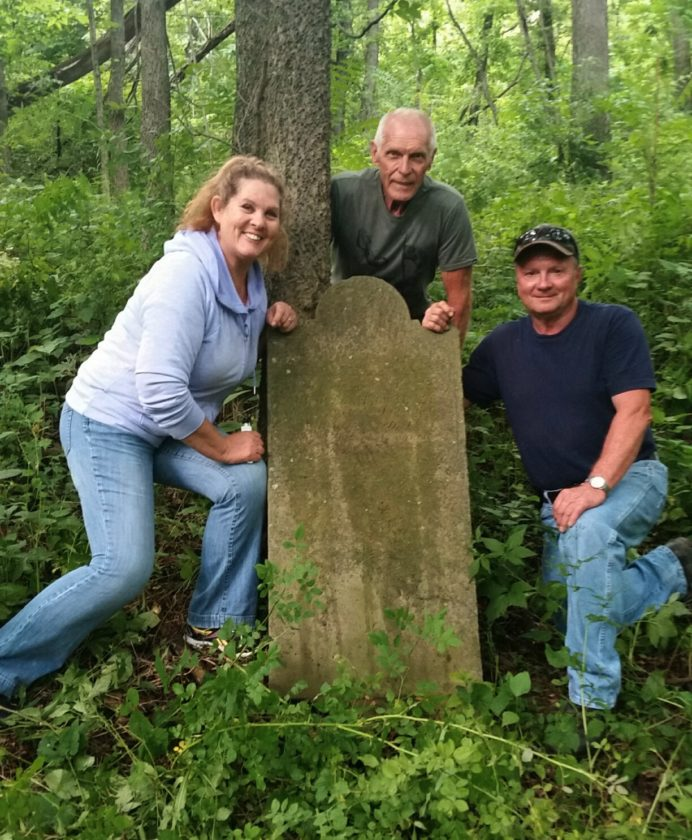 A PRODUCTIVE PURSUIT — With the tombstone of Revolutionary War veteran Benjamin Hall are, from left, Flora L. VerStraten-Merrin, president  of the Wintersville-based Jefferson County Chapter of the Ohio Genealogical Society; Ed Rollandini of the Piedmont area; and Mark Dubil of St. Clairsville. The two hunters and friends connected with VerStraten-Merrin in an effort earlier this year to locate and preserve a Revolutionary War burial site in a remote area of private property in Rush Run, Wells Township, Jefferson County. -- Contributed