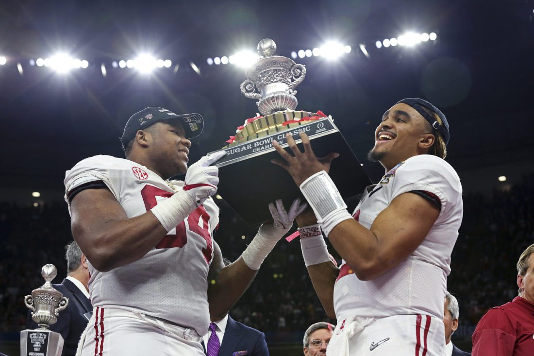 SUGAR WIN — Alabama quarterback Jalen Hurts, right, and defensive lineman Da'Ron Payne hold up the bowl trophy after defeating Clemson in the Sugar Bowl semi-final playoff game for the NCAA college football national championship, in New Orleans Monday. -- Associated Press
