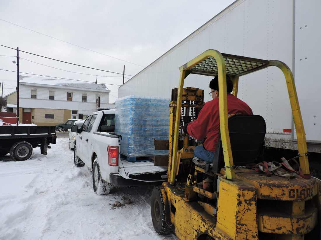HELPFROMCOLUMBUS — Scott Campbell, co-owner of M & M True Value Hardware, used a forklift truck to load bottled water onto 911 Center Executive Director Rob Herrington's pickup truck for delivery to Bergholz. Herrington said the water was sent to assist Steubenville residents dealing with no water issues in the downtown. Some 600 Bergholz residents were also without water Saturday afternoon following a water line break in the village. - Dave Gossett
