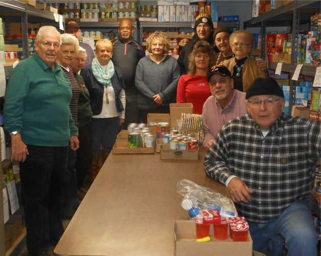 TAKING A BREAK — Volunteers taking a break during a recent distribution day at the Community Bread Basket, 3501 West St., Weirton, were, clockwise, from left, Chuck Utz, Bessie Utz, Betty Trickett, Don Kennedy, Joanne McClain, Greg Mullins, Jan Futey, Easter Noble, Mike Runkel, Thomas Noble, Bob Johnson, Carolyn Johnson and Jim Pauchnik. The organization is in need of volunteers. Anyone interested can call (304) 748-7595. -- Contributed