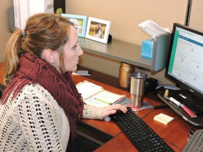 NEW HEADQUARTERS — Lindsay Nolan, a member advocate at the Health Plan, works at her desk inside the company's new downtown Wheeling headquarters. - Casey Junkins