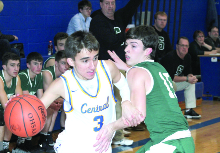 MOVING AROUND — Steubenville Catholic Central's A.J. Connor dribbles past Shenandoah's Kendal Sherman during a boys OVAC semifinal matchup on Tuesday. (Photo by Joe Catullo)