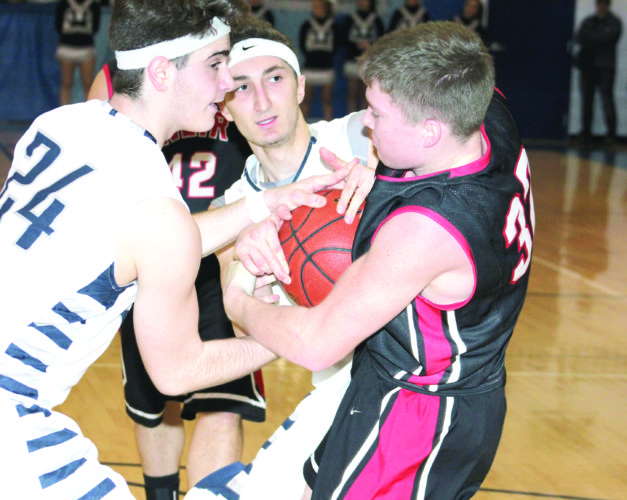 Jake McCoy keeps possession away from Madonna's Lucky Pulice (24) and Tony Sellitti.  (Photo by Joe Catullo)