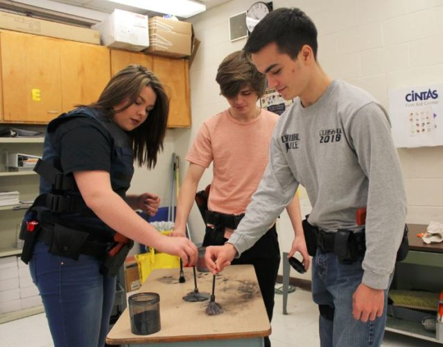 FINGERPRINTING SKILLS — Criminal justice students at the Jefferson County Joint Vocational School show off their abilities with fingerprinting. Seniors Kaitlyn Kennedy, left, Kaleb Shriver, center, Terence O'Neil placed in the crime scene investigation category during the school's Spotlight on Skills competition at the school held Feb. 1 and advanced to the regionals. Other top finishers in the event had a chance to move on to regional and state contests.