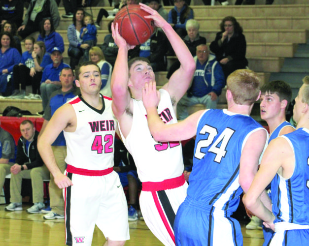 DRIVING IN — Weir High's Reed Reitter (32) looks to shoot in the paint while Nick Keutilla (42) watches against East Liverpool on Friday. (Photo by Joe Catullo)