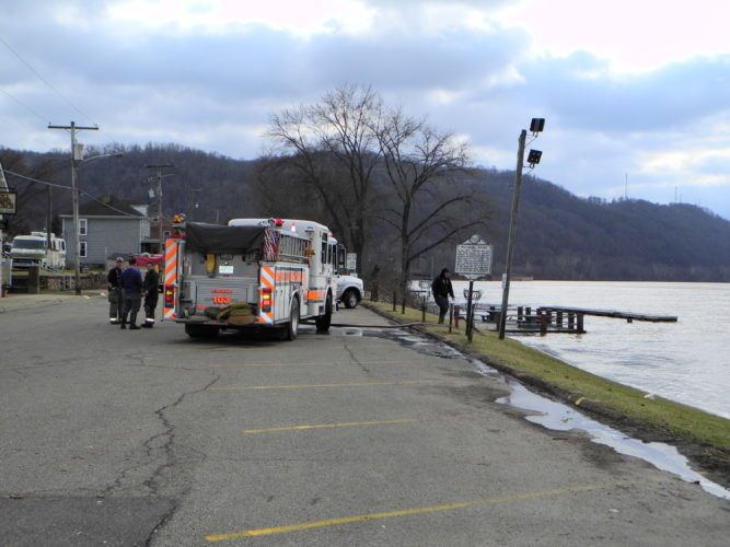 CLEANUPUNDERWAY — Wellsburg firefighters filled a pumper truck with water from the receding Ohio River after washing debris from the Wellsburg Wharf, which had been submerged. Many area emergency personnel and road crews have been cleaning up after this weekend's flood. -- Warren Scott