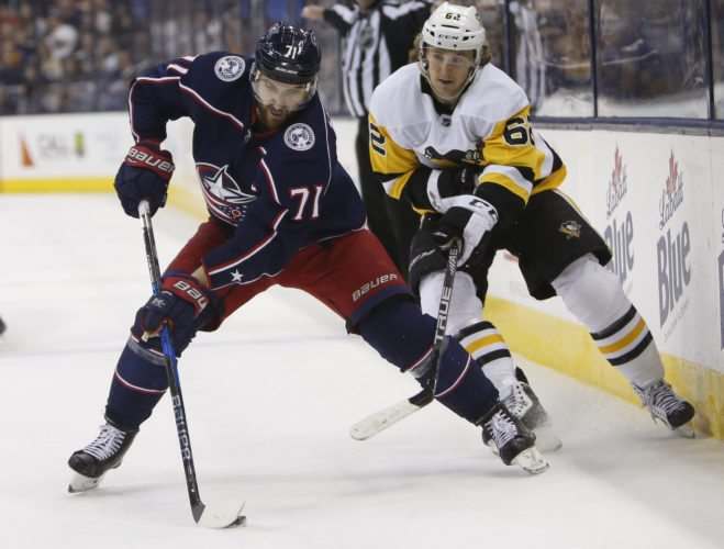 DEFENSE — Pittsburgh's Carl Hagelin looks to stop Nick Foligno during Sunday's game in Columbus. -- Associated Press
