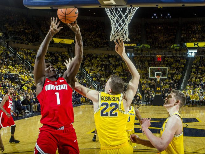 TO THE BASKET — Ohio State's Jae'Sean Tate tries to shoot while defended by Michigan's Duncan Robinson and  Moritz Wagner during Sunday's game. -- Associated Press