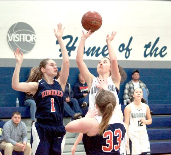 SHOOTING — Madonna's Gab Staffileno attempts a shot over Hundred's Mahala Britton (1) and tori Hawkins (33) during Monday's sectional play-in game at Madonna High School. (Photo by Andrew Grimm)