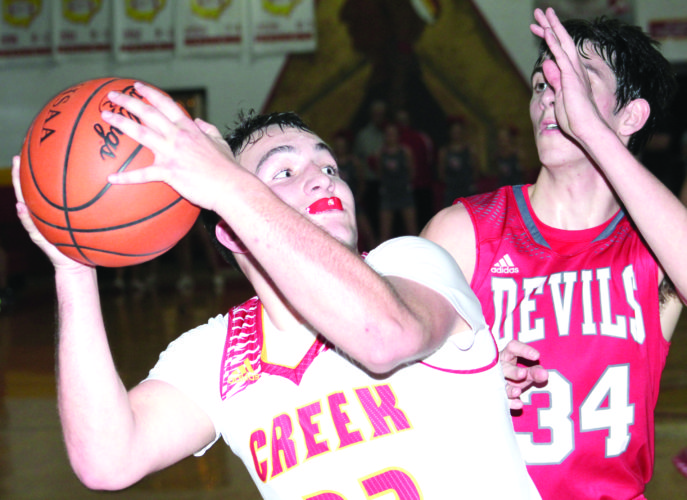 CLOSING IN — Indian Creek's Andy Waggoner attempts a close shot against St. Clairsville's Justin Heatherington on Tuesday. (Photo by Joe Catullo)