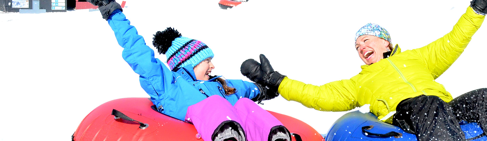 Two Snow Tubers Holding Hands