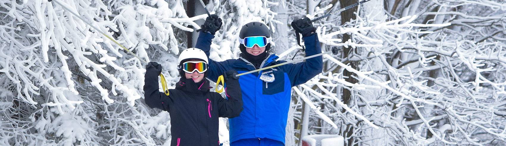 Youth skiers in front of snow covered trees