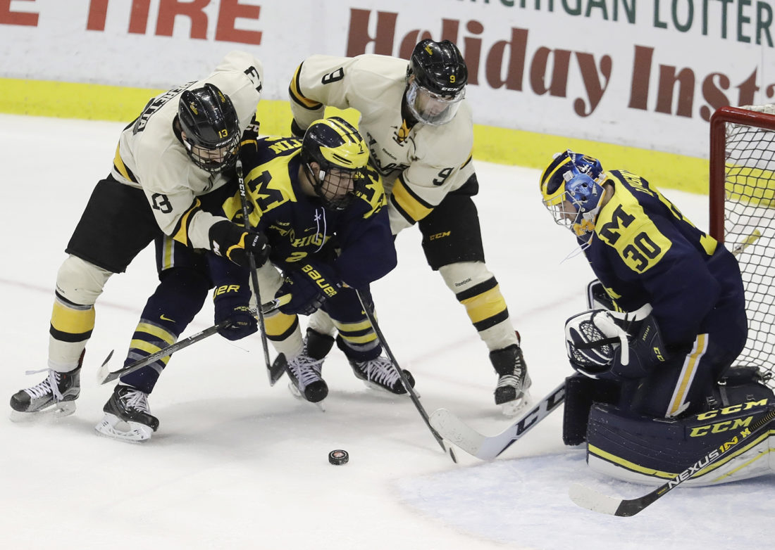 Michigan goalie Hayden Lavigne (30) deflects shot during the second period of the Great Lakes Invitational semifinal against Michigan Tech on Thursday in ...