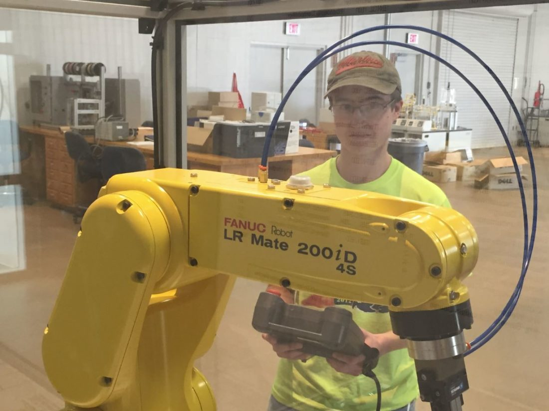 In a file photo, Bay College mechatronics student Andrew Vandermissen works with a Fanuc robot. An agreement between BayCollege and Michigan Tech is part of a project aimed at revamping robotics education.