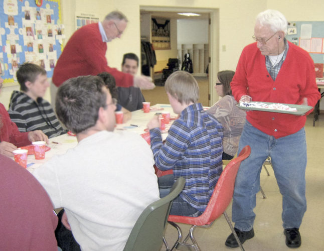 The Golden K will host their Valentine party for special kids on Feb. 13. Pictured is Mike Werner, standing left, and Hank London handing out Valentine cookies at last year's event.