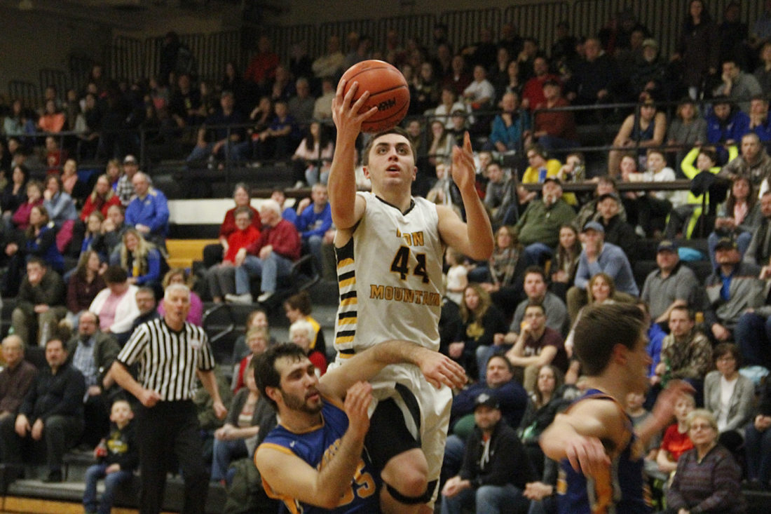 Iron Mountain's Carson Wonders, center, drives to the basket as Kingsford's Owen Petschar, left, and Chase Kreski, right, defend on Tuesday in Iron Mountain. Wonders scored 37 points in the Mountaineers' 73-51 non-conference win. (Adam Niemi/The Daily News)