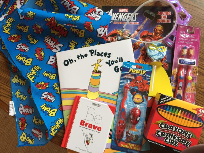 """Edwards Automotive of Iron Mountain is donating  """"Get Well Kits,"""" displaying a super hero or princess theme, to be shared with pediatric patients at Dickinson County Healthcare System. Each box features items such as the book """"Peanuts: Be Brave,"""" a super hero cape, coloring book, crayons, toothbrush, teddy bear, princess crown and fuzzy socks."""