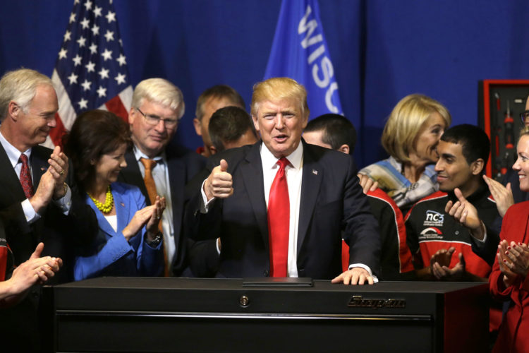 PRESIDENT DONALD TRUMP gives a thumbs-up Tuesday after signing an executive order to tighten the rules for technology companies seeking to bring highly skilled foreign workers to the U.S. while visiting Snap-On Tools in Kenosha, Wis. (AP photo/Kiichiro Sato)