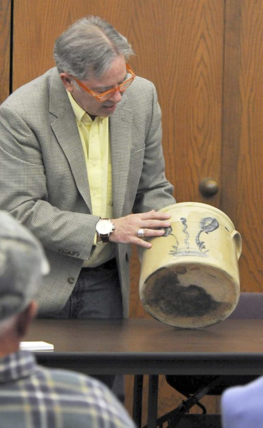 Antiques expert Mark F. Moran examines a piece of stoneware at a past antique appraisal event. He will return to the area in June to conduct appraisals at the Iron River and Iron Mountain libraries.