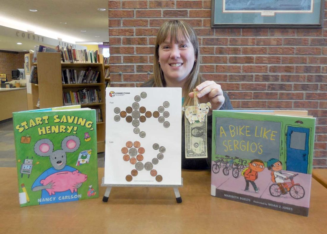 "Children's Specialist Emily Cummings, posing with the books and crafts for ""Money Smart: How to Make Cents."""