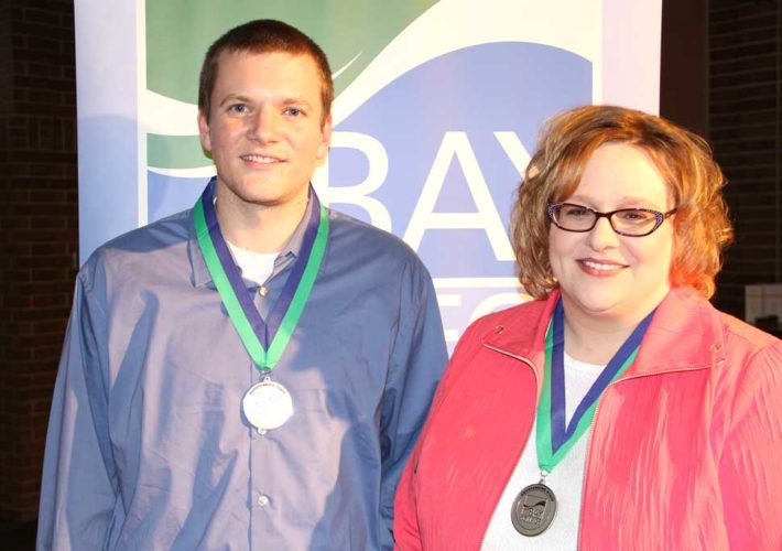JOSH BLUMENSAADT AND Lynn Martinson display the medallions they received for being recognized as the 2017 Outstanding Staff at Bay College.