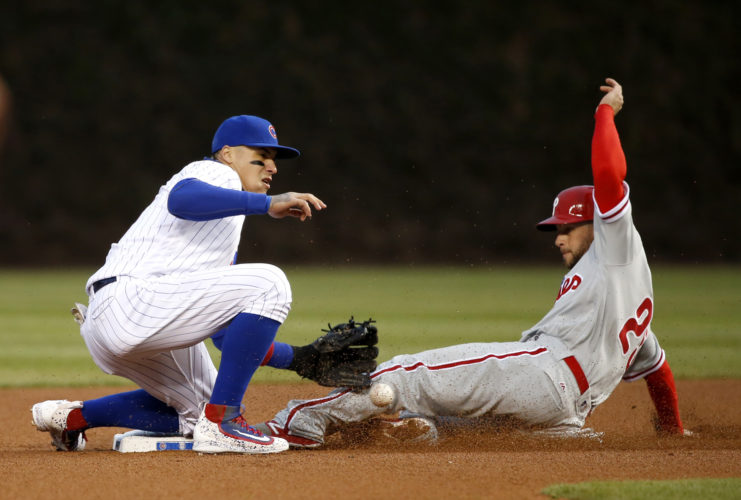 Philadelphia Phillies' Daniel Nava, right, steals second on a throw from Chicago Cubs catcher Miguel Montero to second baseman Javier Baez on Wednesday in Chicago. (AP Photo/Charles Rex Arbogast)