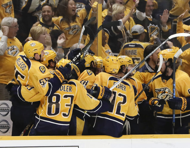 Nashville Predators players celebrate after Calle Jarnkrok, not pictured, scored an empty-net goal against the St. Louis Blues during the third period in Game 6 of a second-round NHL playoff series Sunday in Nashville, Tenn. The Predators won 3-1 to win the series 4-2. It's the first time in franchise history the Predators advanced to the conference finals. (AP Photo/Mark Humphrey)