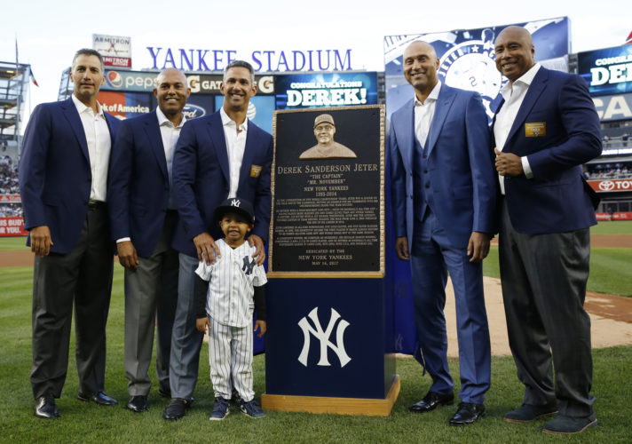 Retired New York Yankees shortstop Derek Jeter, second from right, poses with former teammates from left, Andy Petite, Mariano Rivera, Jorge Posada, and Bernie Williams during a pregame ceremony retiring his number 2 at Yankee Stadium in New York on Sunday. Jeter's nephew Jaden Jeter joined the group. (AP Photo/Pool, Kathy Willens)