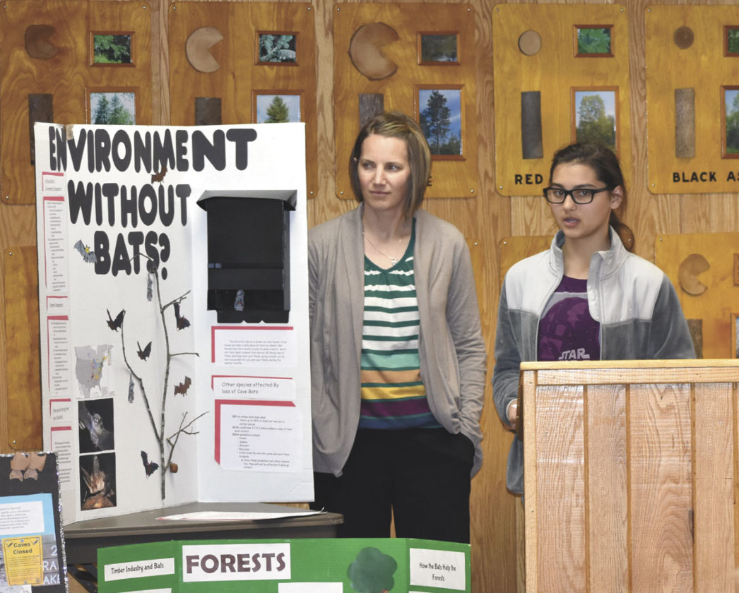 Betsy Bloom/Daily News Photo KENZI GUMMIN, AN eighth-grader in Florence County Schools, describes the agricultural losses and other negative effects that could result from insects if bats became extinct due to white-nose syndrome, a fungus that is decimating bat populations where it has occurred in North America. Teacher Amy Johnson looks on during the presentation to the Federal Sustainable Forestry Committee on Thursday at the Florence Natural Resources Center. Seventh- and eighth-grade students at the Florence school have been researching the effects of the deadly bat disease and strategies for protecting area species such as the now-threatened northern long-eared bat.