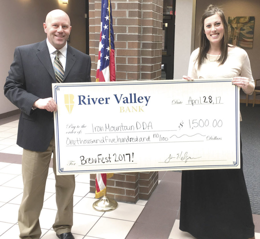 JIM HELGREN OF River Valley Bank presents a check for $1,500 to Paula Craven, Downtown Iron Mountain program director for the Brew Fest event in Iron Mountain on June 10. The group, Norton, Chartier & Company, has agreed to play for the new event, which will be centered at the downtown stage located across from the Dickinson County Library in Iron Mountain.