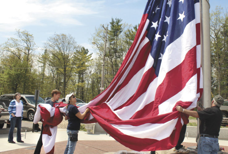Santina Johnson, left, observes as Lori Massicotte, Sue Starr and Jim Starr, all of Iron Mountain, raise a new garrison flag Friday atop Pine Mountain at the Upper Peninsula Veterans Memorial. The flag was purchased in honor of fallen soldier Pfc. Ronald A. Michaud of Niagara, Wis., a Silver Star recipient who was killed in action in Vietnam on June 20, 1967. Johnson, a niece to Michaud, was present to honor her uncle.   Theresa Proudfit/Daily News Photos