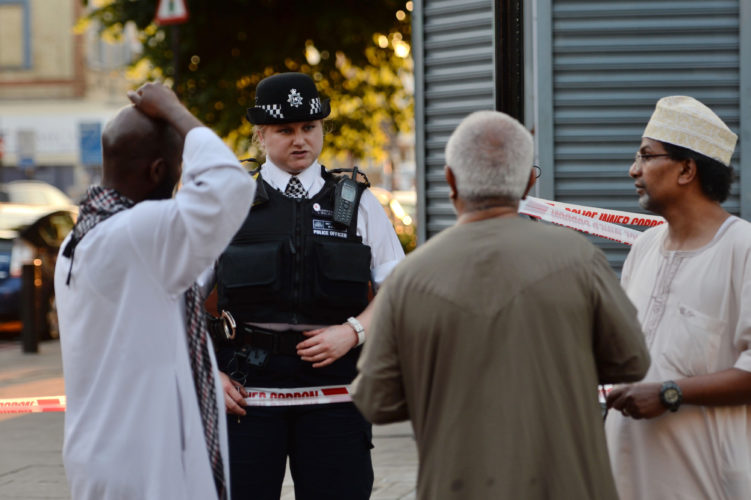 Victoria Jones/PA via AP  A POLICE OFFICER talks to residents at Finsbury Park in north London after a driver plowed a van into a crowd of people leaving a mosque early today. One man died at the site and 10 people were injured.