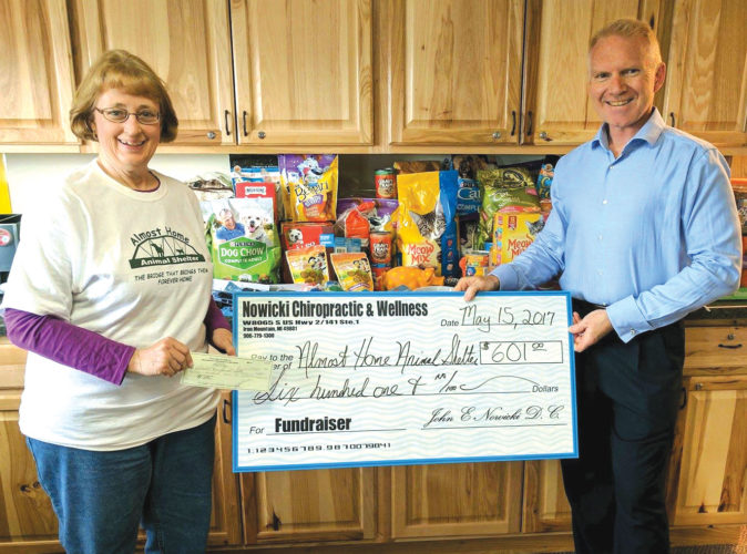 JOAN RECLA, OF the Almost Home Animal Shelter staff, accepts a donation of items and a check for $601 from Dr. John Nowicki of Nowicki Chiropractic & Wellness in Iron Mountain.