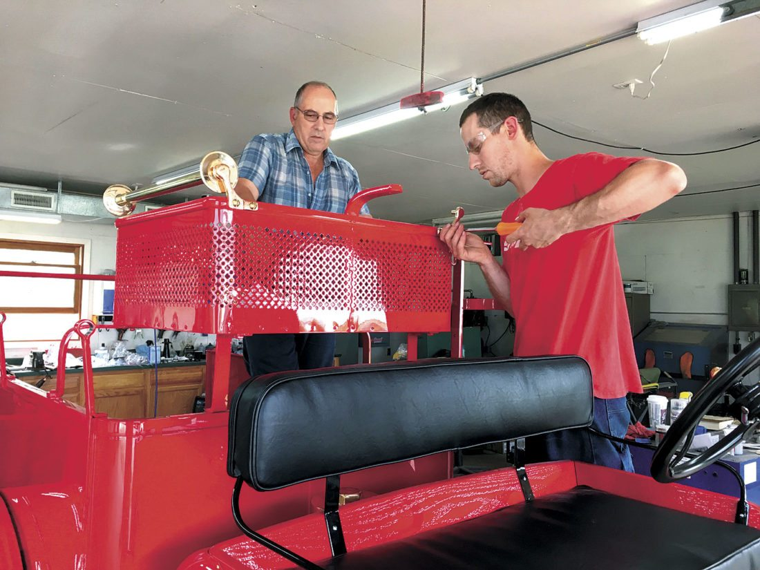 DANIEL ZOPPETTI AND his father, John, at left, put some of the final touches on Florence's antique fire truck. The restored 1917-18 vehicle will be unveiled Sunday in Florence. (Submitted photo)