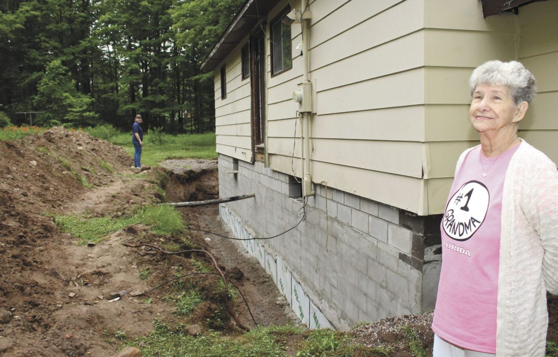 Becky Bishop and Blanche Lantz stand outside the Lantz house where a new wall was constructed after flooding destroyed the Felch basement.   Theresa Proudfit/Daily News Photo