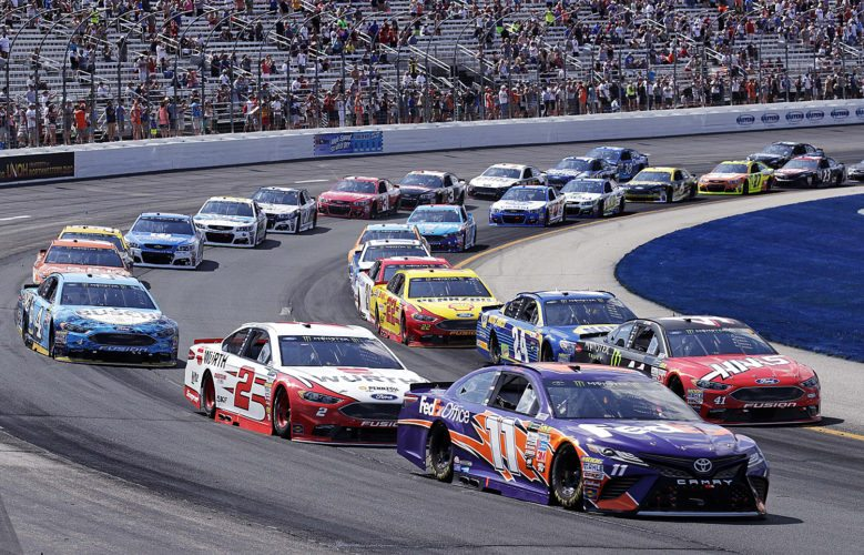 Driver Denny Hamlin (11) and the pack race during the NASCAR Cup Series 301 auto race at the New Hampshire Motor Speedway in Loudon, N.H. on Sunday. Hamlin won the race. (AP Photo/Charles Krupa)