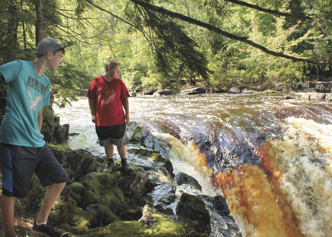 PINE RIVER FALLS has three separate tiers below the Pine River Flowage Dam. Evan Tregillis and Luke Ruble, both of Iron Mountain, look out from Tier 2. (Theresa Proudfit/Daily News photo)