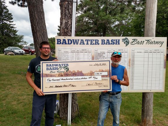 Kyle Komorowski, left, and Mike Komorowski of Oak Creek, Wis., hold their $1,316 check for winning the Badwater Bass Tourney with 15.1 pounds of bass caught and released.