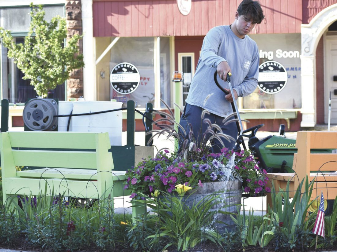 ZACK CAUDELL, 21, waters the pocket park area off the city parking lot on Hughitt Street in downtown Iron Mountain. The area annually is planted and maintained by the Downtown Beautification Committee, which is responsible for dozens of hanging baskets and sidewalk planters throughout the downtown, plus several small areas like the pocket park. On dry days, Caudell and his brother, Riley, will make the rounds with hundreds of gallons of water for the plants. (Betsy Bloom/Daily News photo)