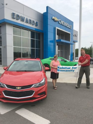 NANCY PELLEGRINI, EXECUTIVE director for Habitat for Humanity Menominee River, is shown here with JD Edwards of Edwards Automotive and the 2017 Chevrolet Cruze donated for the hole-in-one prize during the annual golf outing.