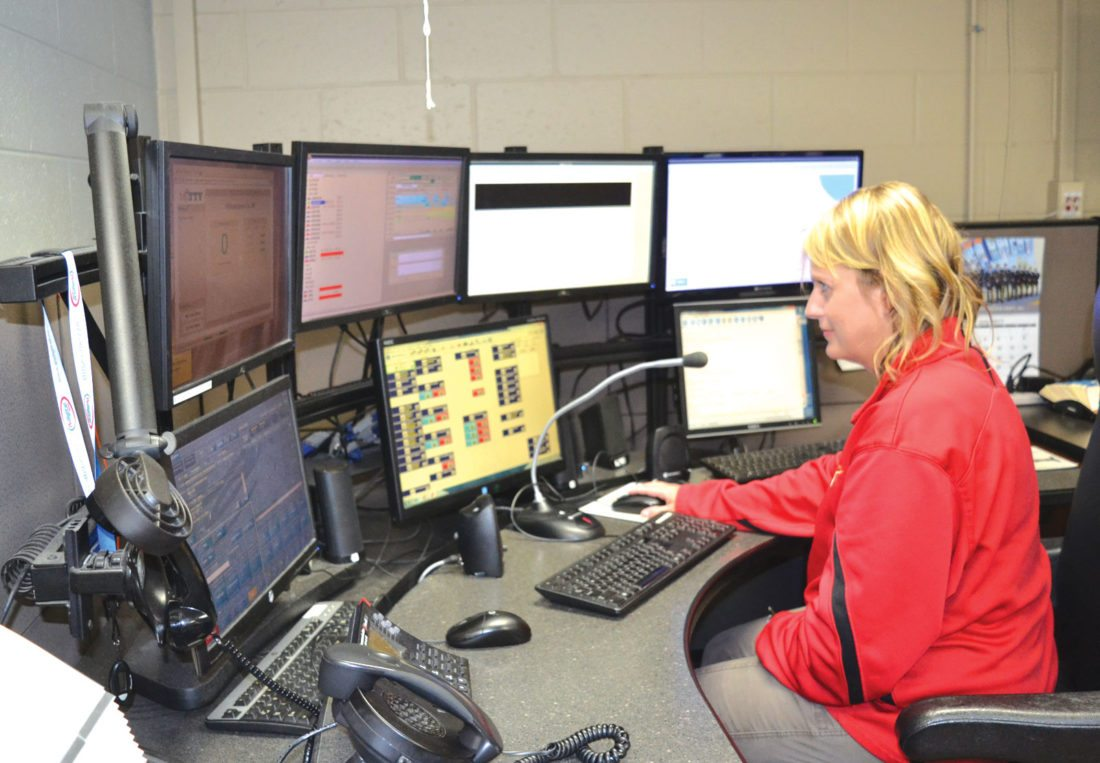 Amy Zeeb monitors seven computer screens of emergency services information at the 911 dispatch center in the Dickinson County Sheriff's Office in Iron Mountain.  (Nikki Younk/Daily News Photos)