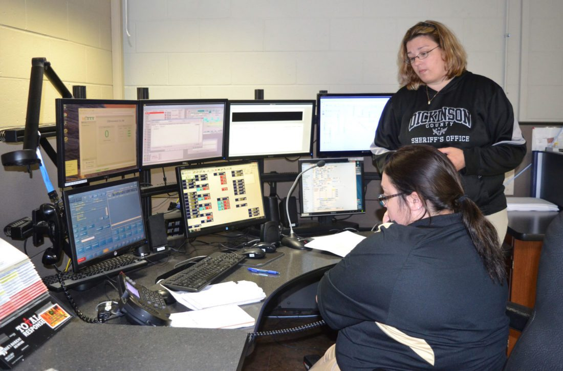 Dickinson County Dispatcher Christine Erkkila, standing, listens in as her trainee, Morgan Mattord, answers a call at the 911 dispatch center in the Dickinson County Sheriff's Office in Iron Mountain. Statistics provided by Dickinson County Sheriff Scott Rutter show the dispatch center handled almost 3,800 911 calls and about 22,000 non-911 calls since the beginning of the year.  The monthly break-down for 911 calls and non-911 calls is 342 and 2,800 in January, 448 and 2,461 in February, 516 and 3,000 in March, 476 and 2,842 in April, 604 and 3,119 in May, 694 and 3,867 in June, and 719 and 3,616 in July.