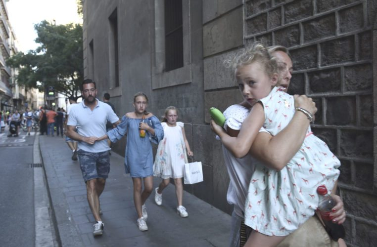 PEOPLE FLEE IN Barcelona, Spain, after a white van jumped the sidewalk in the historic Las Ramblas district and crashed into a summer crowd of residents and tourists, killing 13 and injuring 100, police said. (AP Photo/Giannis Papanikos)