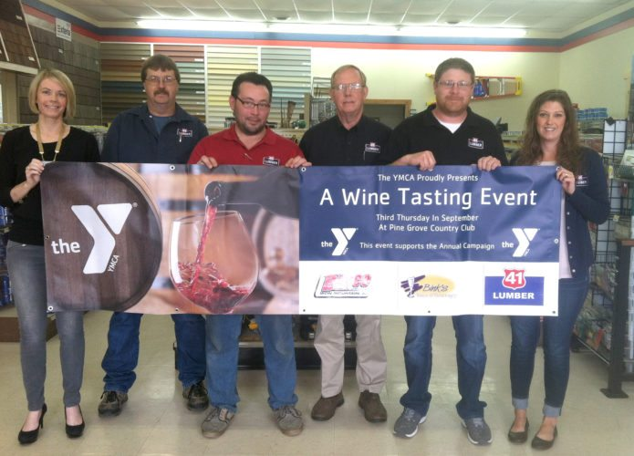 Employees from 41 Lumber display the Corks and Forks banner. The Quinnesec retailer is the signature sponsor of this year's Corks and Forks fundraiser for the Northern Lights YMCA. Pictured, from left are Carol Quandt, Craig Burkman, Paul LeMay, Steve Quandt, Jake Johnston, and ­­Erika Harnden.