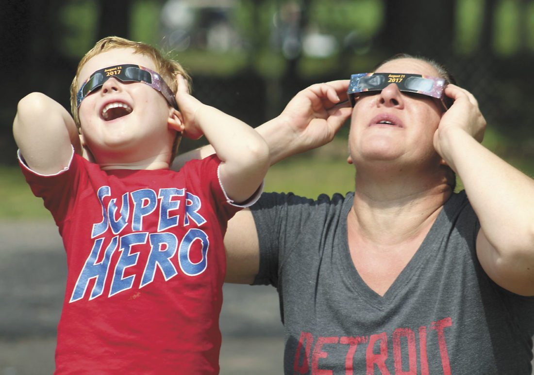 LIAM AND JULIE BURIE of Kingsford watch the solar eclipse from the City Park in Iron Mountain. (Theresa Proudfit/Daily News photo)