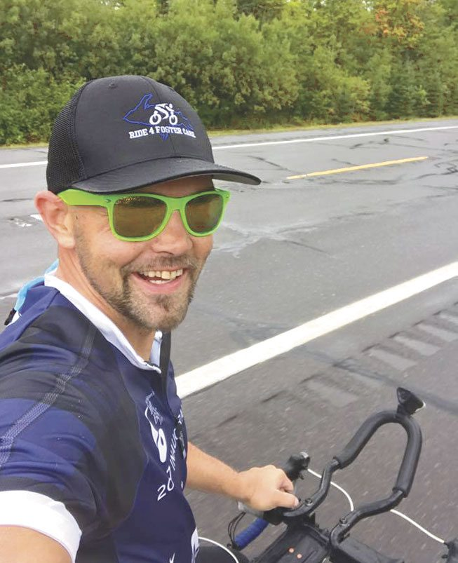 JOHN KOLBAS OF Iron Mountain had to stop his ride to Mackinac Bridge last week due to injury. The ride raises money to support foster children taking part in sports and other activities.