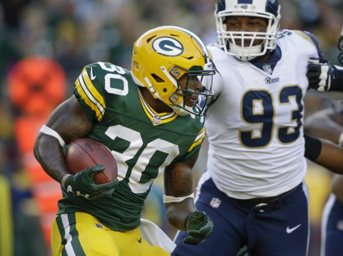 Green Bay Packers' Jamaal Williams runs past Los Angeles Rams' Ethan Westbrooks (93) during the first half of a preseason game Thursday in Green Bay, Wis. (AP Photo/Jeffrey Phelps)