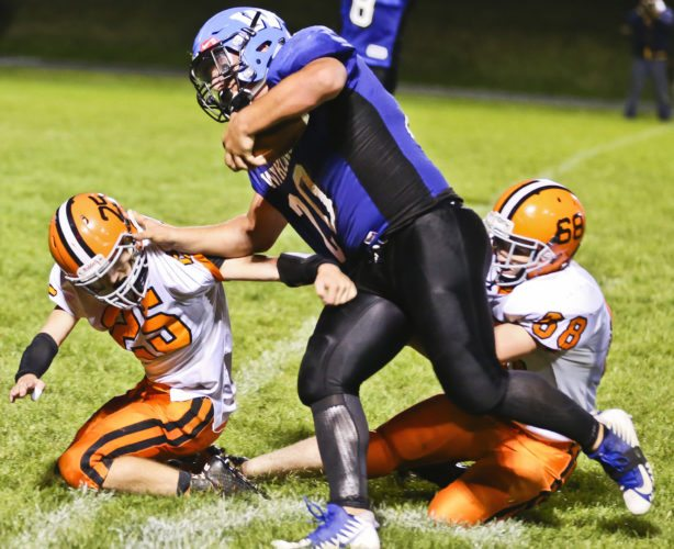 Hurley defenders Dakota Haanen, left, and Forest Wiedbrauk try to bring down West Iron County's Jayce Brockhagen Friday night at Nelson Field in Iron River. He rushed for 225 yards. (Jason Juno/The Daily Globe)